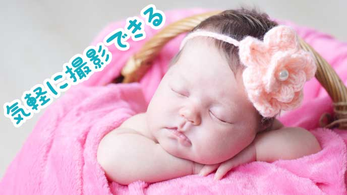 毛糸の花飾りをつけて眠る赤ちゃん