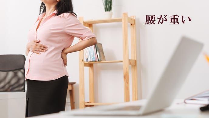 腰に手を当てる妊婦