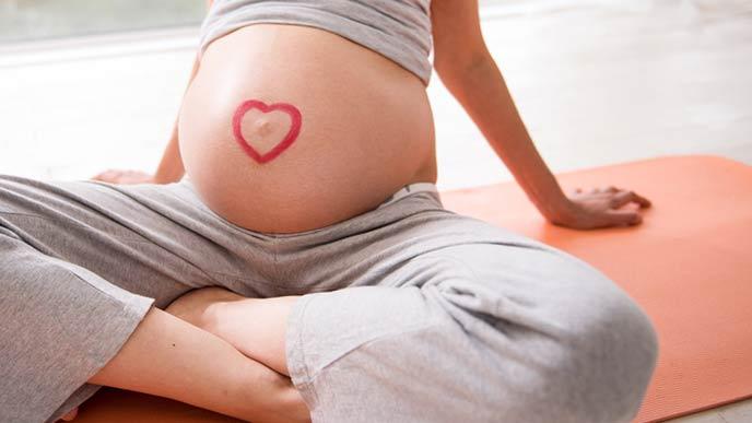 床にマットを敷いて座る妊婦
