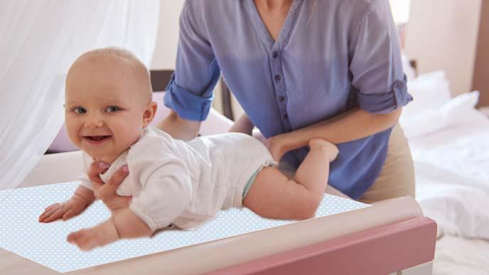 おむつ替えシートの上に赤ちゃんをのせるお母さん