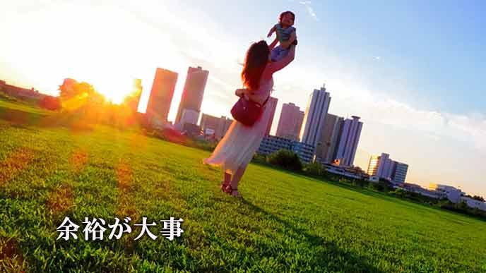 公園の芝生で子供を空に向かって抱え上げる女性