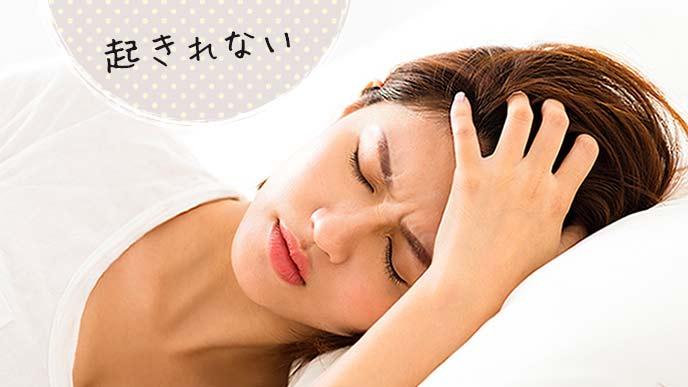 ベッドの上で頭を押さえて不快な表情の女性