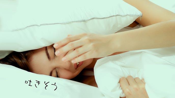 吐き気を我慢しながら寝ている女性