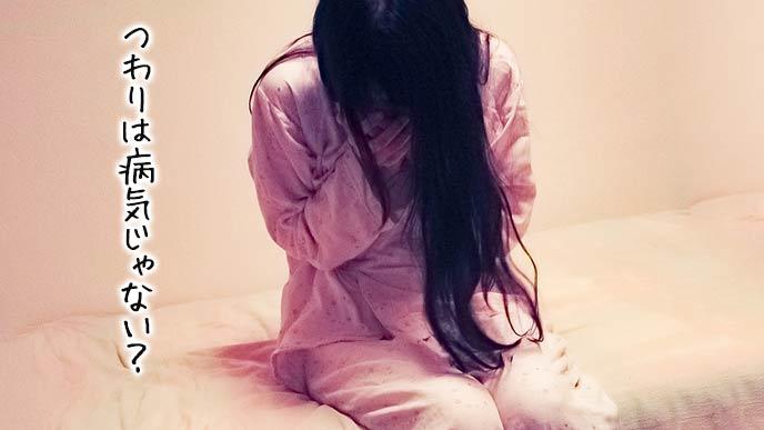 ベッドに座り込んで口を押さえる妊婦
