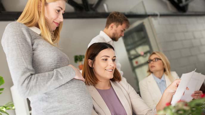 職場で同僚に相談する妊婦