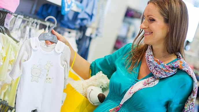 赤ちゃんの衣類を買い物する妊婦