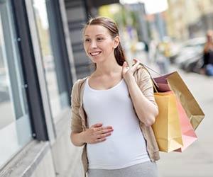 町の商店街を歩く妊婦