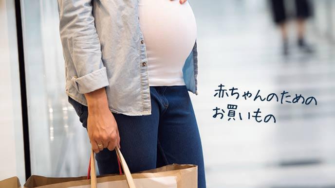 紙袋を下げて歩く妊婦