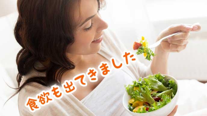 美味しそうにサラダを食べている女性