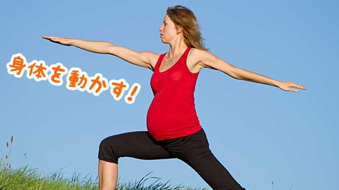外でマタニティヨガをしている妊婦