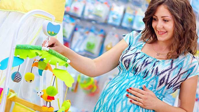 赤ちゃん用のおもちゃを見ている妊婦
