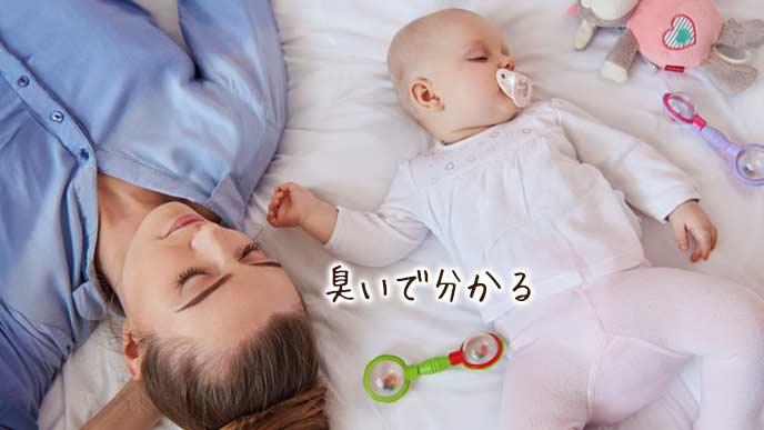 赤ちゃんの傍で横になる母親