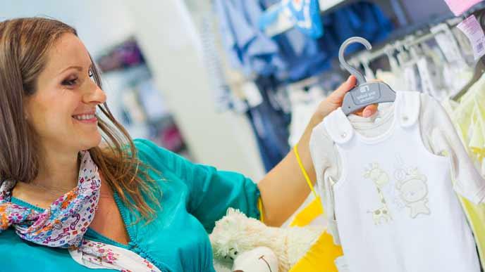 店でベビー服を品定めする妊婦