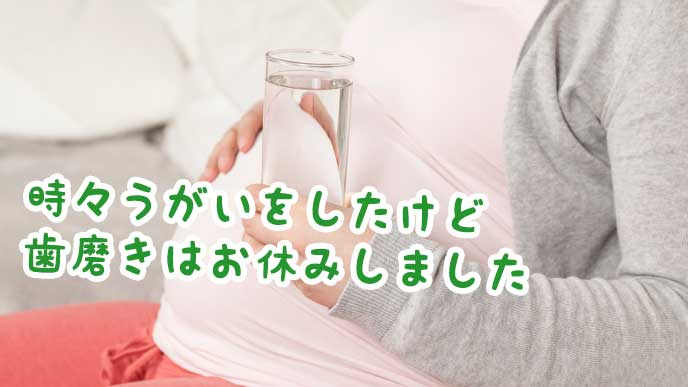 水が入ったコップを持っている妊婦