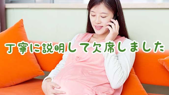お腹を撫でながら電話をしている妊婦