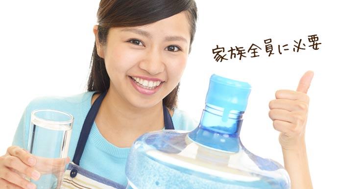 水の替えボトルの前でコップを持つ女性