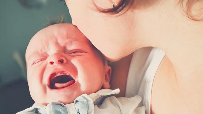 泣く赤ちゃんにキスする母親