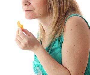 チーズ一切れを口に運ぶ妊婦