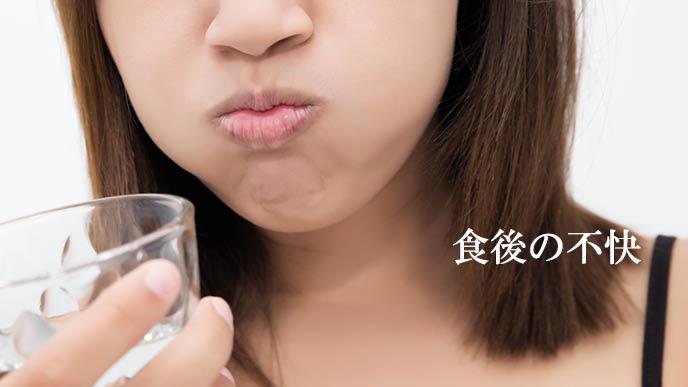 食後に水で口をすすぐ女性