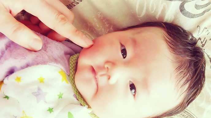 赤ちゃんの頬を指で触る母親