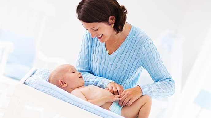 バスタオルに赤ちゃんを乗せる母親