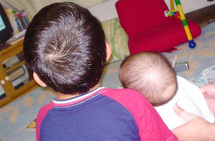 お兄ちゃんと並んで座ってる赤ちゃん