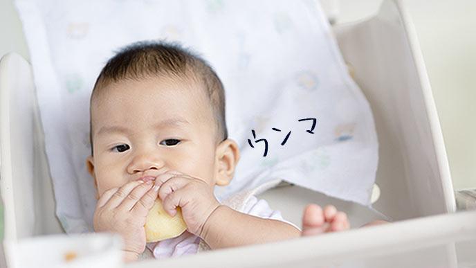 リンゴを手づかみで食べる赤ちゃん