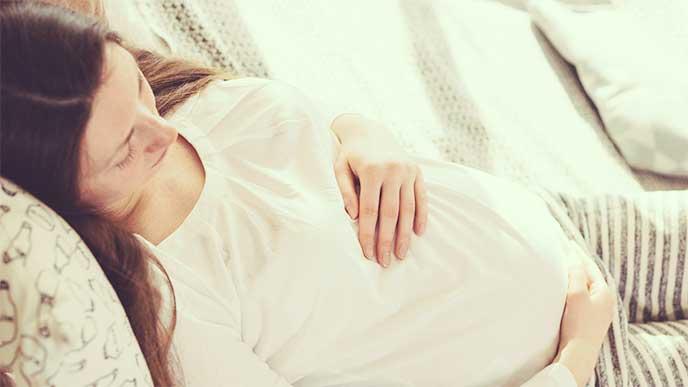 横になってお腹を触っている妊婦さん