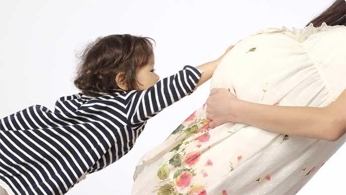 妊娠した母親の大きなお腹を触ってる女の子