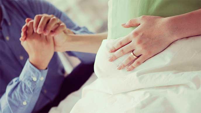 出産を控えて入院してる奥さんの手をにぎる旦那さん
