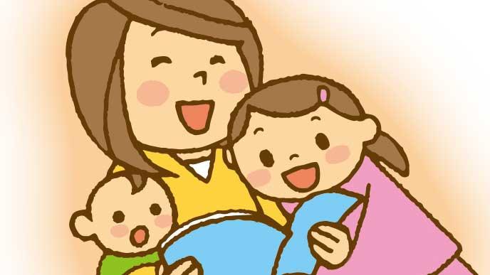 小さな二人の子供を一緒に本を見てる笑顔の母親