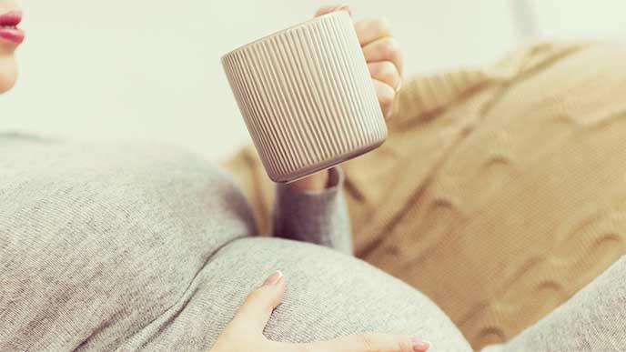 温かい飲み物を飲んでる妊婦さん