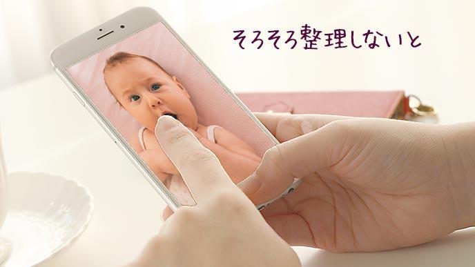 スマホ内の赤ちゃんの写真を見る母親