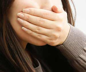口を手で押さえる女性