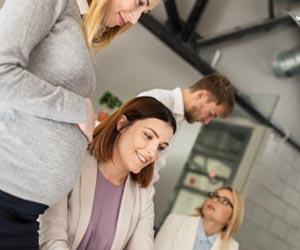 職場で同僚と働く妊婦