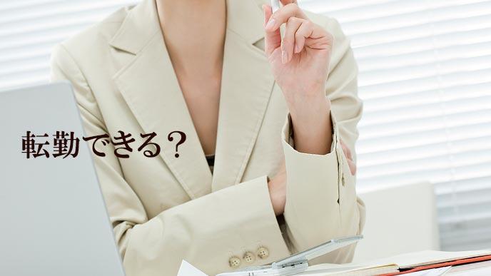 職場のデスクで転勤の可能性を考える女性