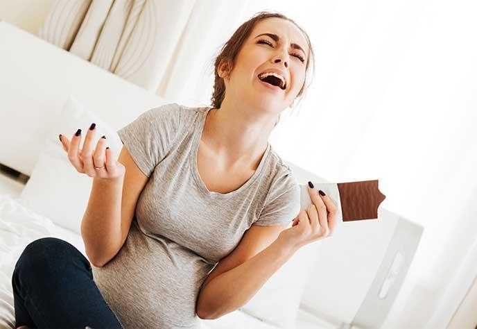チョコレートを食べて喜んでいる妊婦さん