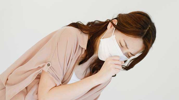 マスクをしてくしゃみをしてる女性