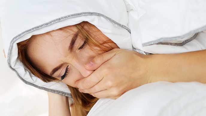 布団にくるまりながらもつわりで吐きそうになってる妊婦さん