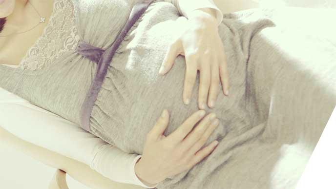 お腹を触って胎動を感じてる妊婦さん