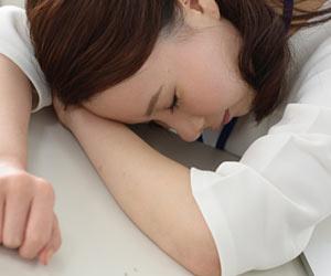 疲れて机に腕枕して休む女性