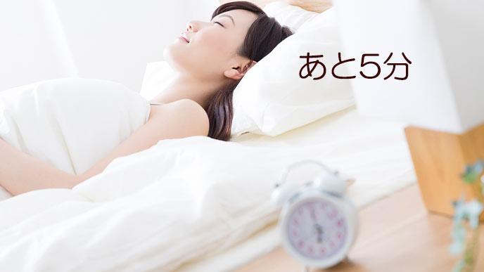 目覚まし時計の傍で眠り続ける女性
