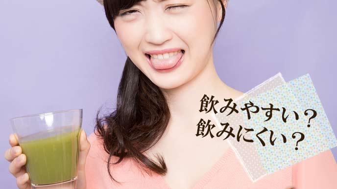 青汁を飲んで苦そうに舌を出す女性