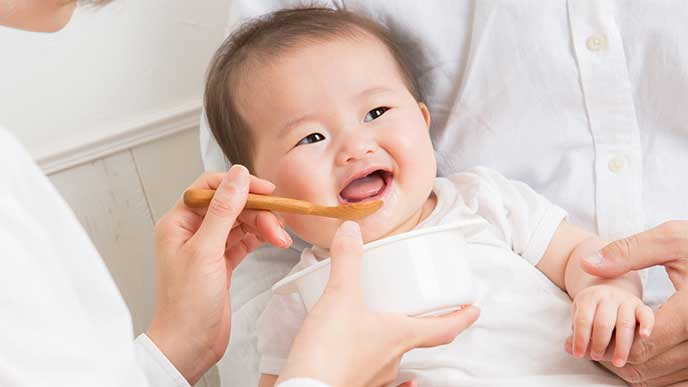 スプーンで湯冷ましを飲ませてもらって笑顔の赤ちゃん