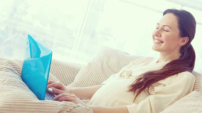 パソコンを使ってる笑顔の妊婦さん