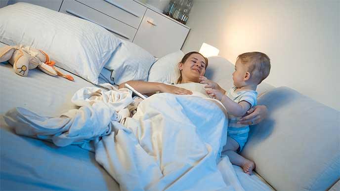 電気スタンドに照らされる赤ちゃんと母親