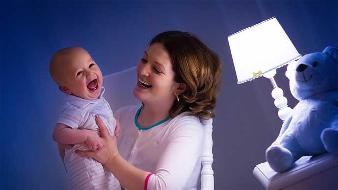 電気スタンドの明かりではっきり見える赤ちゃんを抱っこしてるママ