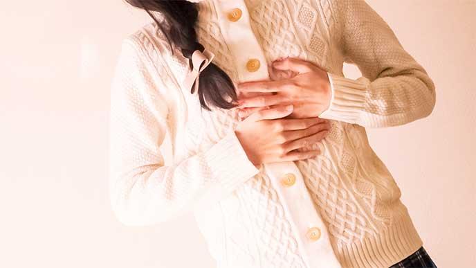 胸を手で押さえている女性