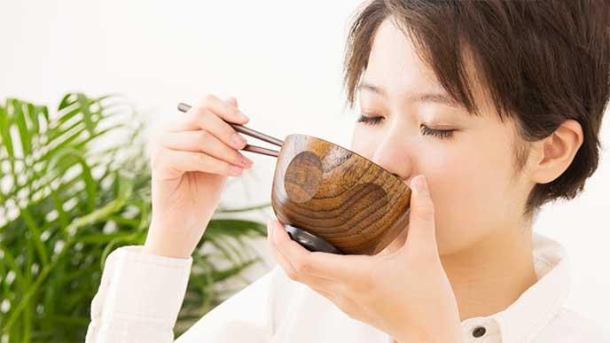 味噌汁を飲んでる女性