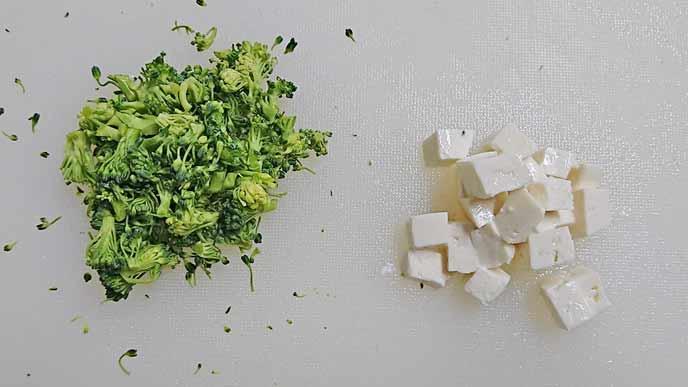 まな板の上にある細かく刻まれたブロッコリーと賽の目の豆腐